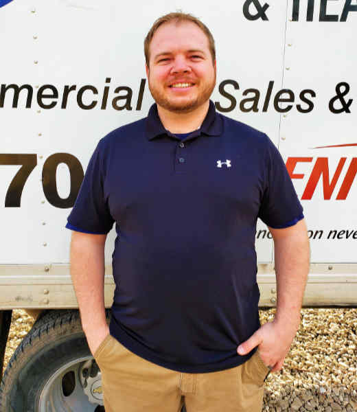 Tony Koth, owner of Tom's Air Conditioning, standing in front of a service truck