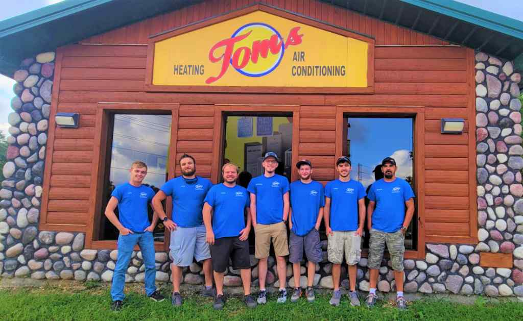 Tom's air conditioning and heating repair experts standing in front of the shop.